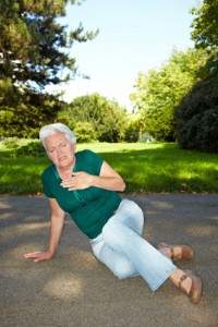 Herzkranke Seniorin im Park fasst sich an die Brust