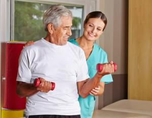 Senior hebt Hanteln bei Physiotherapie neben einer Krankenschwester